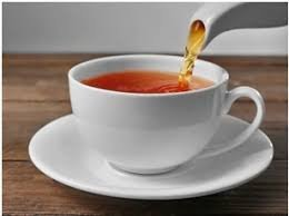a teacup pouring tea into a white cup with saucer