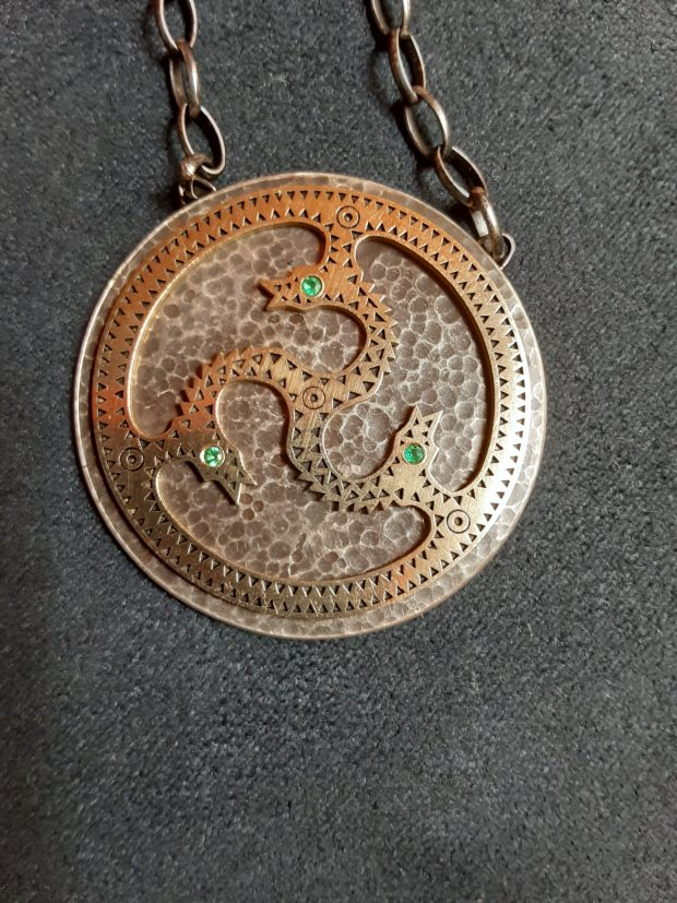 front of the amulet showing emerald eyes